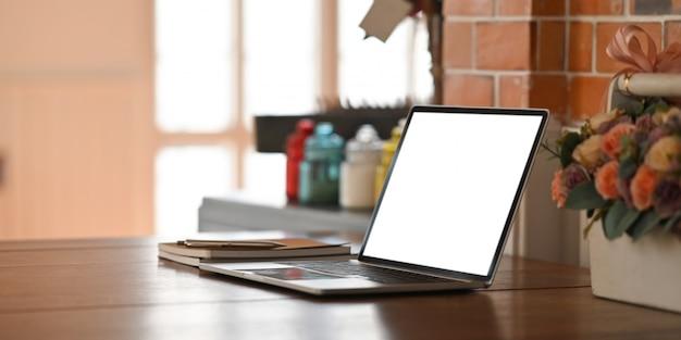 Ordenador portátil con pantalla en blanco blanco poniendo en mesa de madera con cuaderno, bolígrafo y cesta de flores sobre pared de ladrillo vintage. Foto Premium