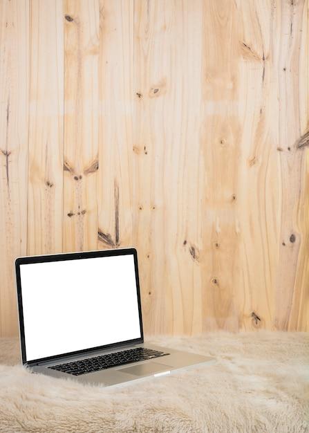 Ordenador portátil con pantalla en blanco en blanco sobre piel suave frente a pared de madera Foto gratis