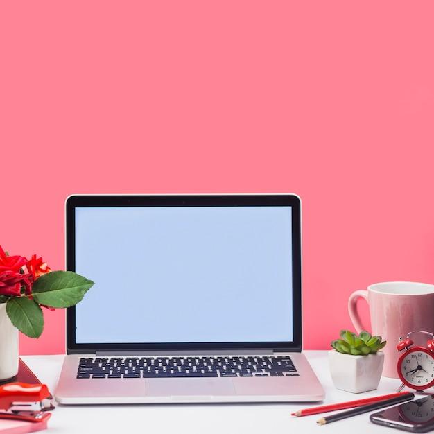 Ordenador portátil con taza y flores en la mesa Foto gratis