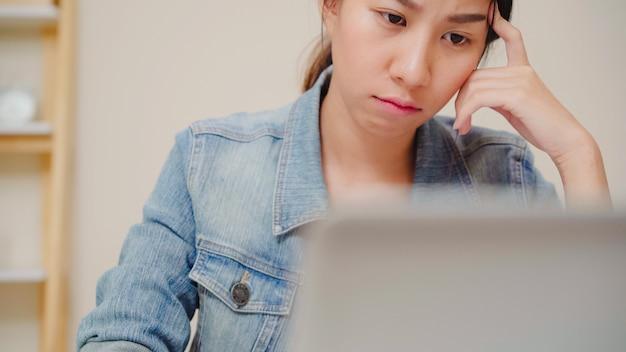 Ordenador portátil de trabajo sonriente de la mujer asiática joven hermosa en el escritorio en sala de estar en casa. finanzas y calculadora del documento del cuaderno de la escritura de la mujer de negocios de asia en ministerio del interior. Foto gratis