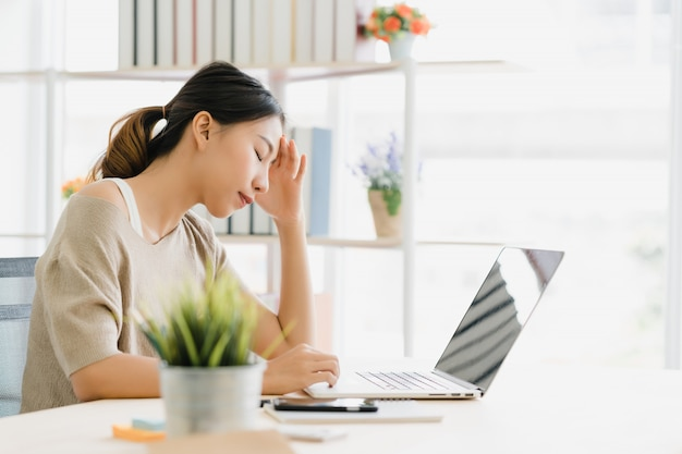 Ordenador portátil de trabajo sonriente de la mujer asiática de los jóvenes hermosos en el escritorio en sala de estar en casa Foto gratis
