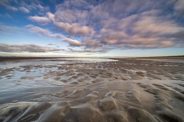 Orilla húmeda con pequeños charcos de agua bajo un cielo nublado azul Foto gratis