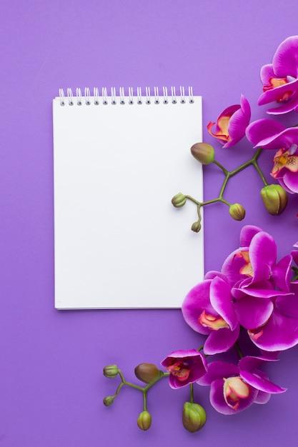 Orquídeas moradas con bloc de notas de espacio de copia Foto gratis