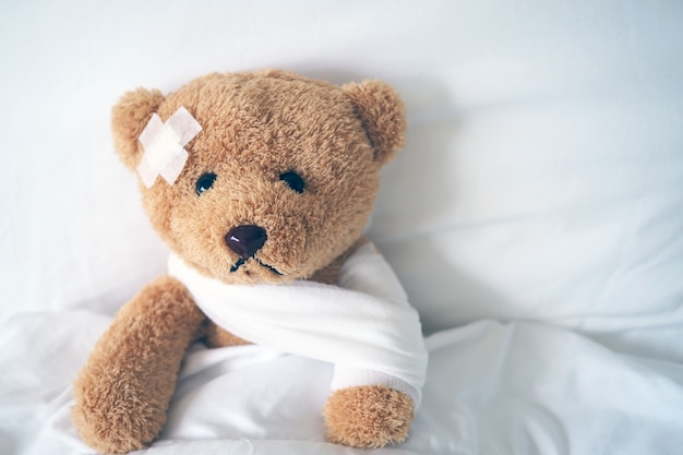 Oso de peluche acostado enfermo en la cama con una diadema y un paño cubierto Foto Premium