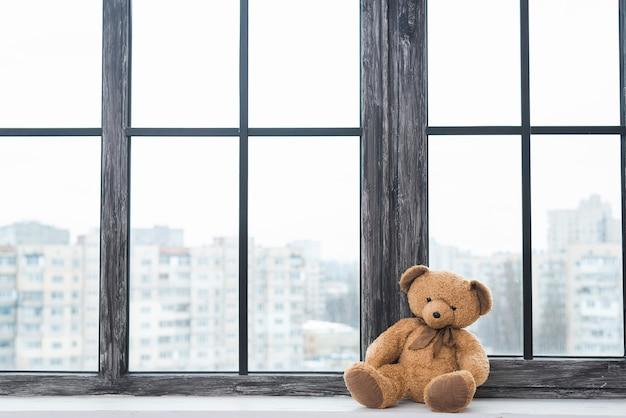 Oso de peluche solitario sentado cerca del alféizar de la ventana cerrada Foto gratis