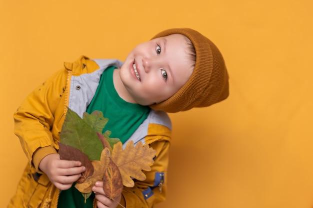 Otoño. bebé sonriente con hojas amarillas en la mano. moda estacional. ropa de otoño moda infantil. hoja cae. niño en ropa dorada, sombrero naranja Foto Premium