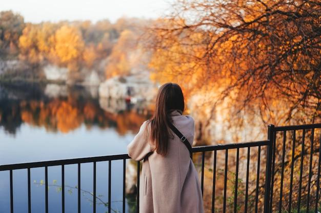 Otoño niña de pie hacia atrás y mirando la naturaleza. Foto gratis