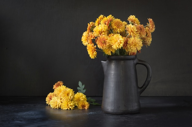 Otoño oscuro naturaleza muerta. otoño con flores de crisantemo amarillo en florero de barro en negro. Foto Premium