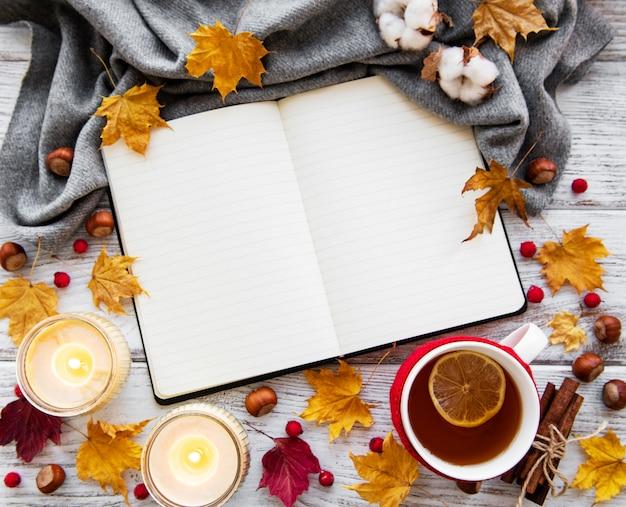 Otoño plano con cuaderno, taza de té y hojas. Foto Premium