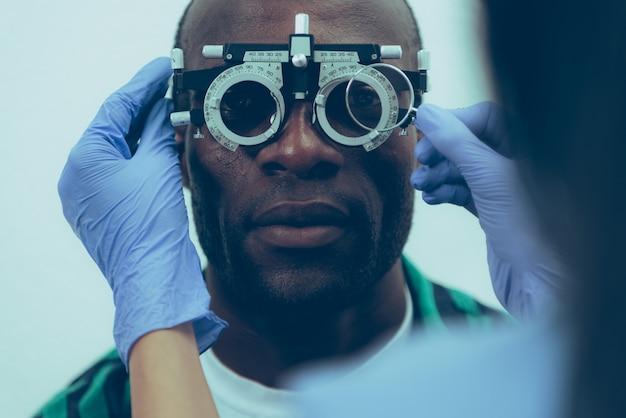 Paciente adulto de sexo masculino en examen óptico en clínica Foto Premium