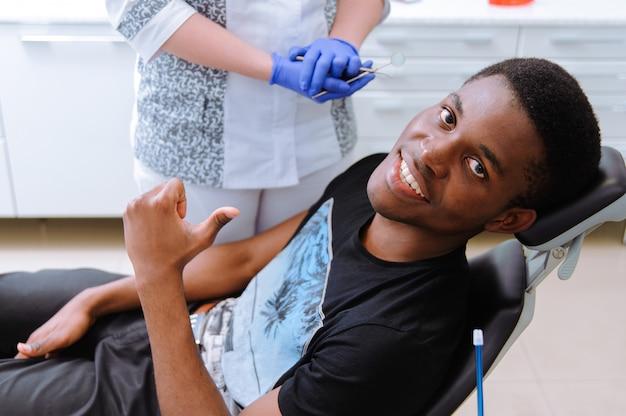 Paciente africano en odontología sonriendo en silla dental Foto Premium