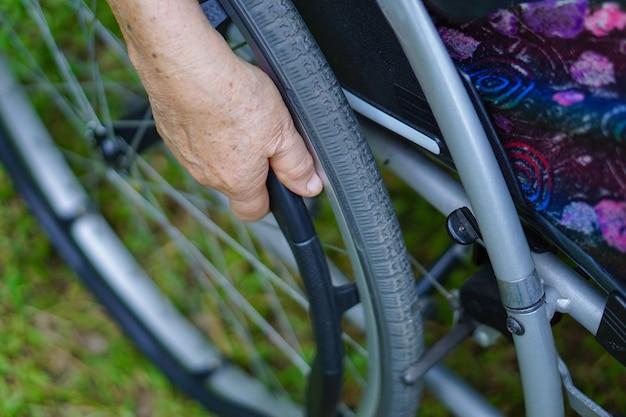Paciente asiático mayor de la mujer en la silla de ruedas en parque. Foto Premium