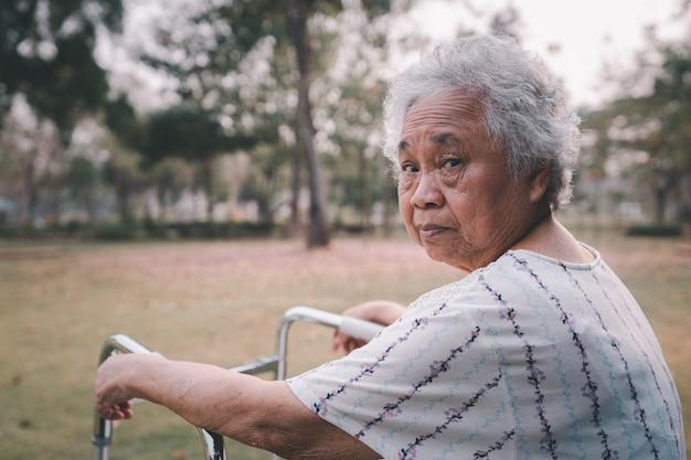 Paciente asiático mayor o anciano mujer caminar con andador en el parque con espacio de copia, concepto médico fuerte y saludable Foto Premium