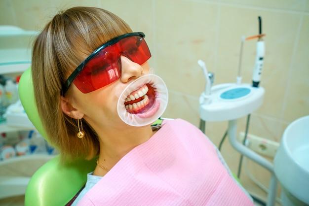 Paciente feliz de la odontología en la silla en gafas. Foto Premium