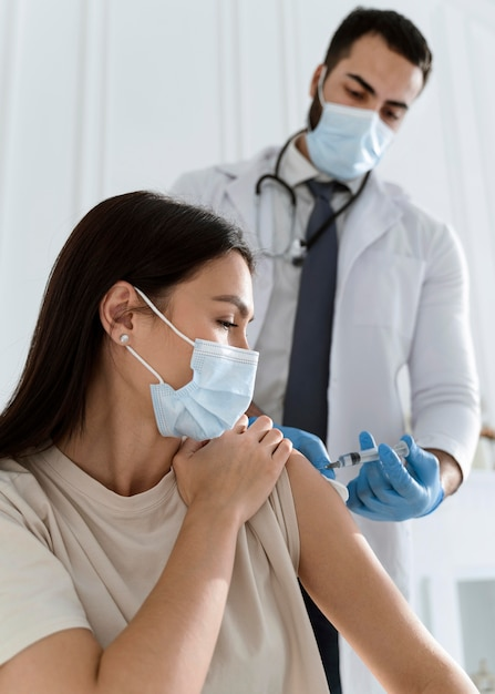Paciente joven con máscara médica siendo vacunado por médico Foto gratis