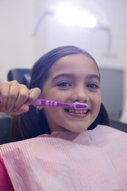 Paciente joven que se cepilla los dientes Foto Premium