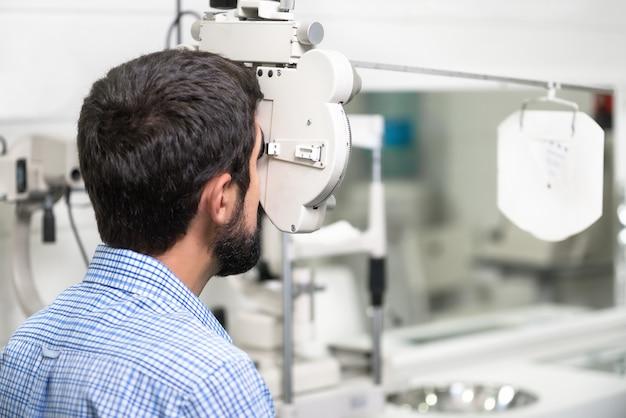 El paciente está leyendo el cuadro del optometrista en la clínica de oftalmología moderna. Foto Premium