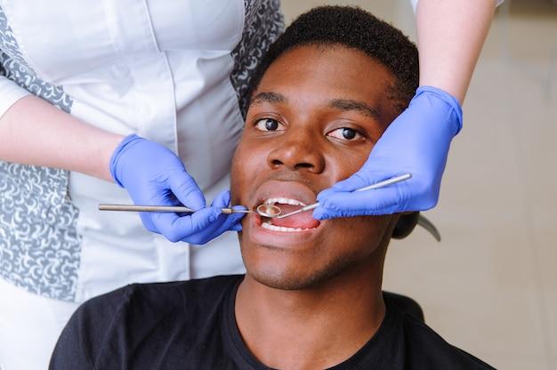 Paciente masculino africano recibiendo tratamiento dental en clínica dental Foto Premium