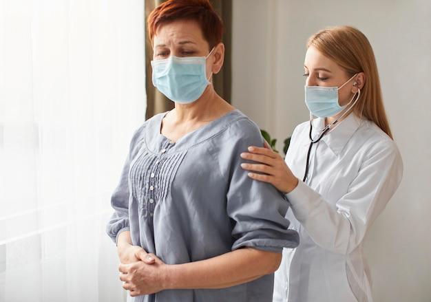 Paciente mayor con máscara médica y centro de recuperación covid doctora con estetoscopio Foto gratis