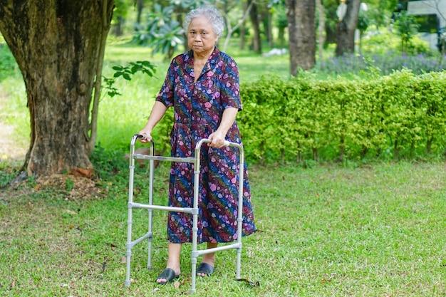 Paciente mujer asiática senior dama caminar con andador en el parque. Foto Premium