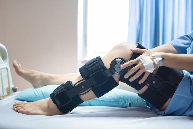 Paciente mujer asiática con vendaje compresión compresión rodillera lesión en la cama en el hospital de enfermería. asistencia médica y asistencia médica. Foto Premium