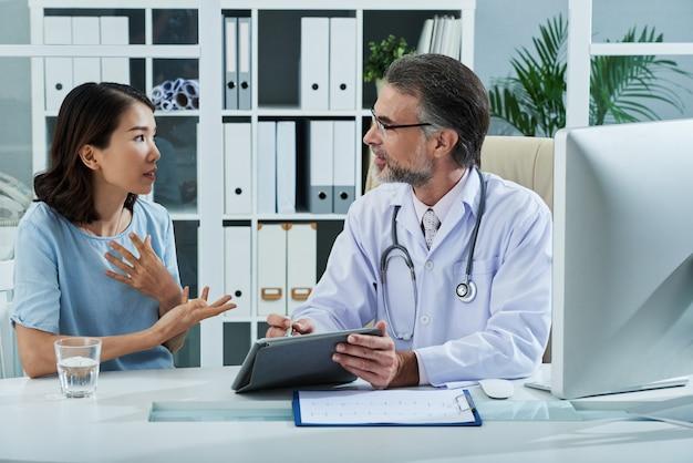 Paciente que le dice al médico acerca de los síntomas de la enfermedad Foto gratis