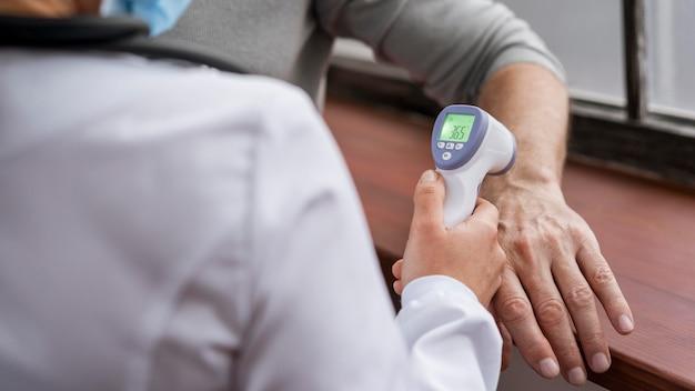 Paciente que tiene su temperatura controlada Foto gratis