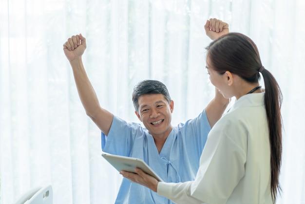 Paciente senior asiático en cama de hospital discutiendo con doctora Foto Premium
