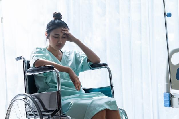 Paciente serio sentado en silla de ruedas en el hospital. Foto Premium