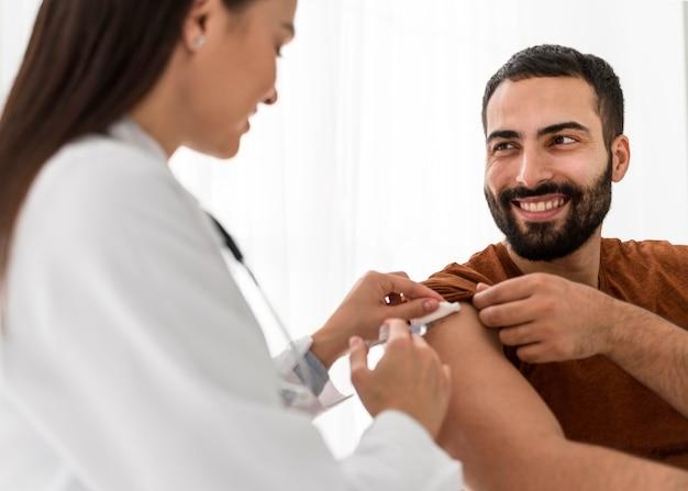 Paciente sonriente mirando a la doctora Foto gratis