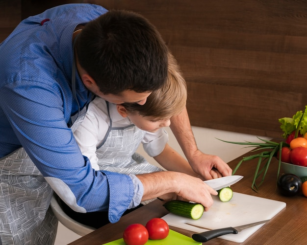 Padre de alto ángulo enseñando a hijo a cortar verduras Foto gratis