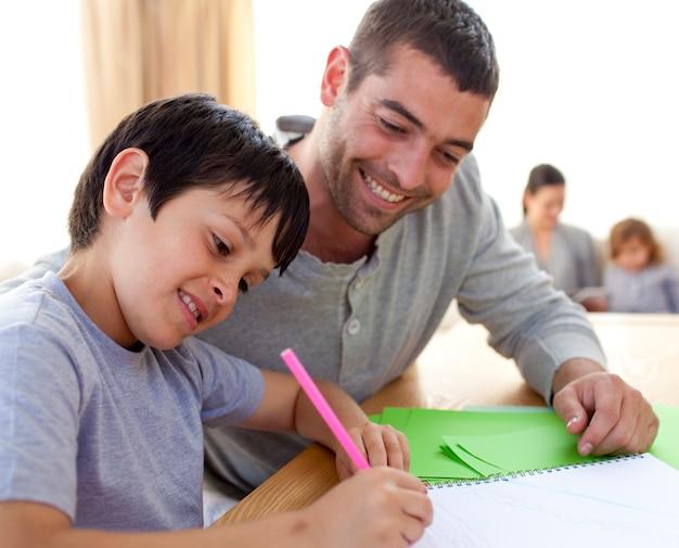Padre ayudando a su hijo a hacer la tarea | Foto Premium