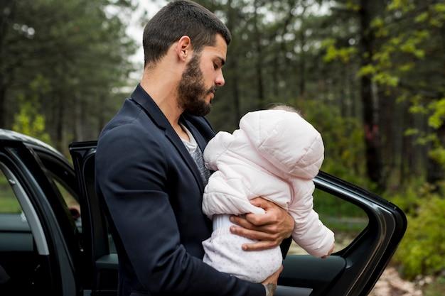 Padre barbudo con bebé cerca de coche Foto gratis