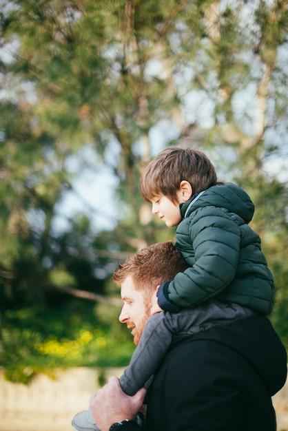 Padre cargando hijo en hombros Foto gratis