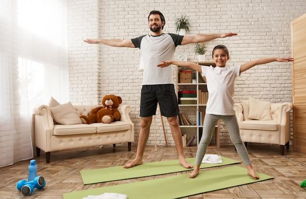 Padre caucásico e hija hacen ejercicios de estiramiento en casa Foto Premium