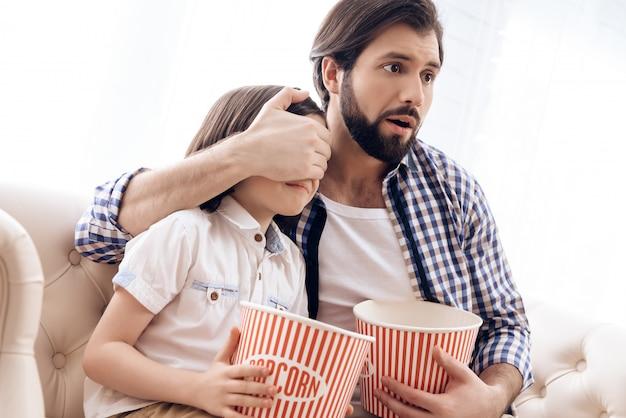El padre cierra los ojos del hijo mientras ve una película de terror. Foto Premium