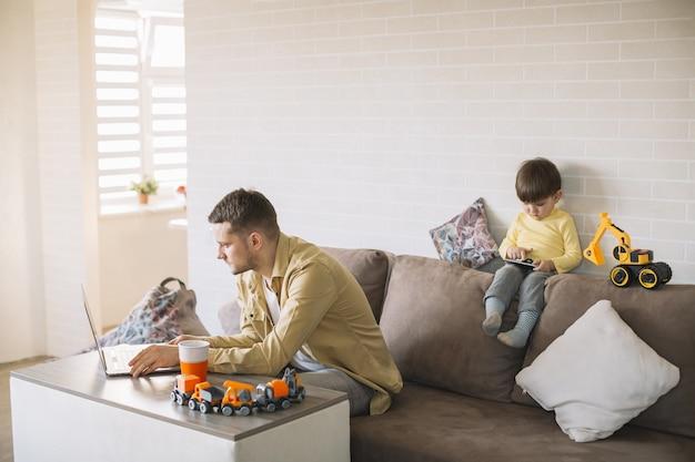 Padre comiendo y trabajando desde casa larga vista Foto gratis