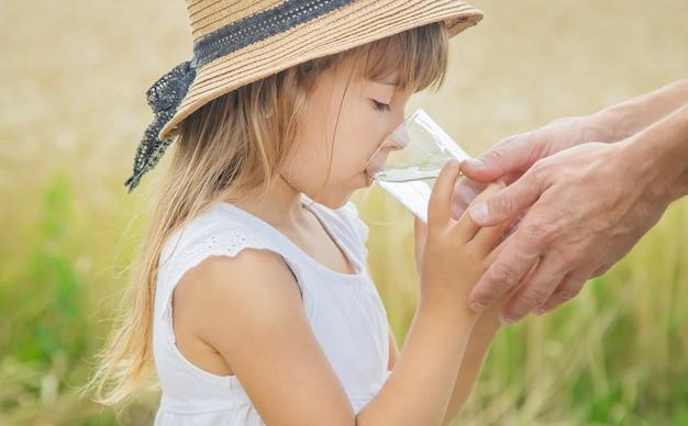 El padre le da agua al niño en el fondo del campo. Foto Premium