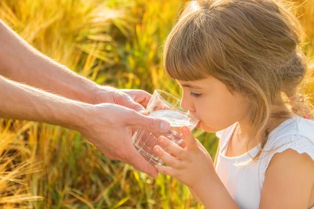 El padre le da al niño un vaso de agua. enfoque selectivo Foto Premium