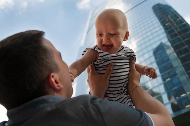 Padre e hija de un año contra el cielo y los rascacielos. viajar con niños, el desarrollo de la inteligencia emocional. Foto Premium