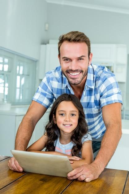 Padre e hija usando tableta digital en casa Foto Premium