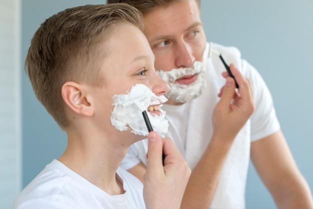 Padre e hijo afeitado en la vista lateral del baño Foto gratis