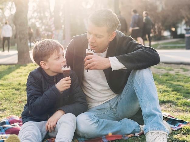 Padre e hijo comiendo helado Foto gratis