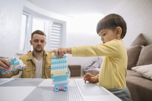 Padre e hijo construyendo un auto Foto gratis