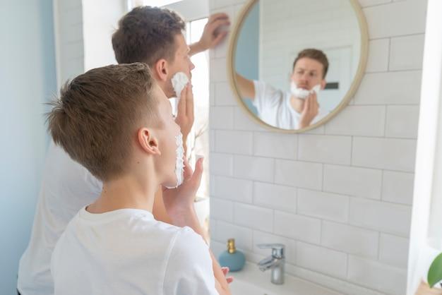 Padre e hijo con crema de afeitar sobre la vista del hombro Foto gratis