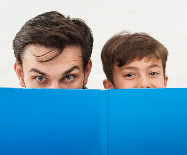 Padre e hijo cubriéndose la cara con un libro azul Foto gratis