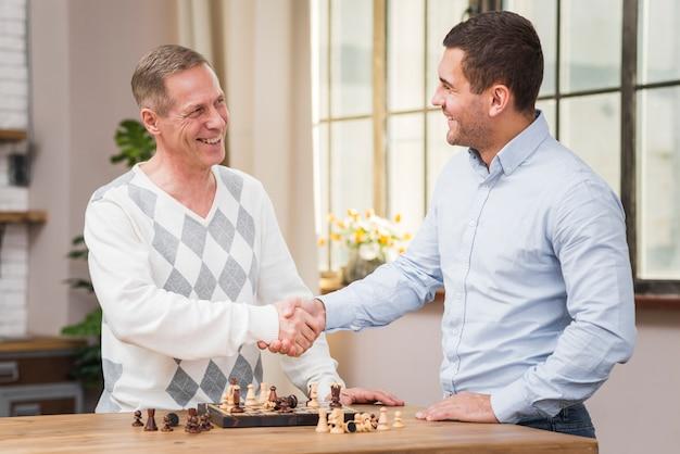 Padre e hijo estrechándole la mano después de un partido de ajedrez Foto gratis