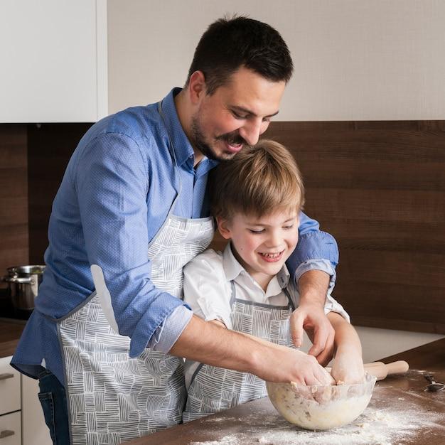 Padre e hijo haciendo masa juntos Foto gratis