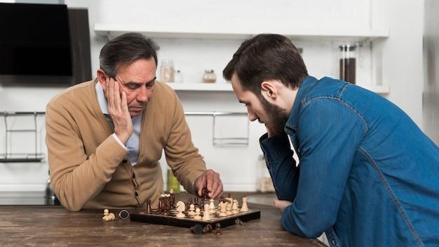Padre e hijo jugando al ajedrez en kithcen Foto gratis