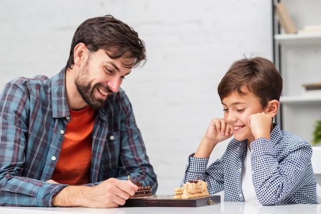 Padre e hijo jugando al ajedrez Foto gratis